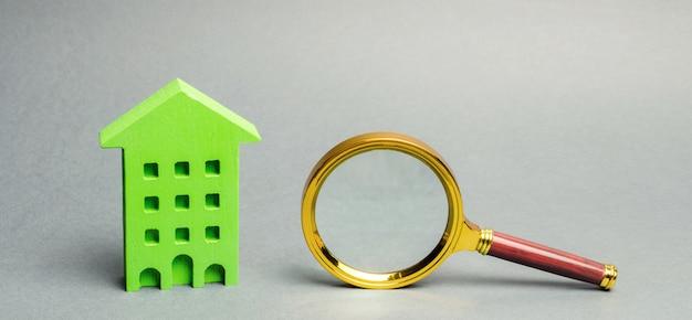 Miniaturowy drewniany dom i szkło powiększające.