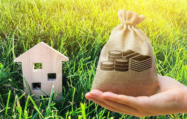 Miniaturowy drewniany dom i worek pieniędzy na trawie.