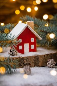 Miniaturowy drewniany dom na śniegu nad niewyraźną świąteczną dekoracją