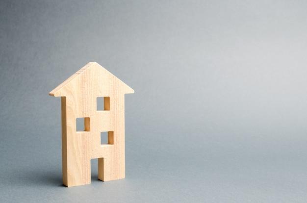 Miniaturowy drewniany dom na szarym tle.