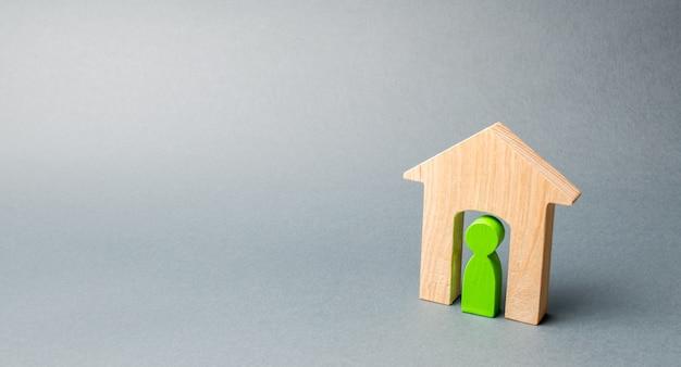 Miniaturowy drewniany dom z najemcą w środku.