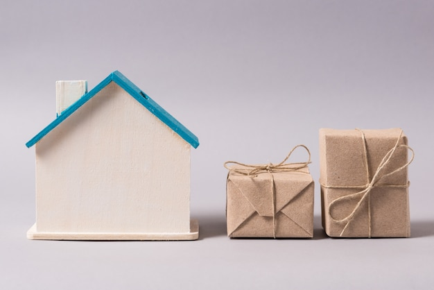 Miniaturowy drewniany domek, symbol, ze skrzynkami, dostawa do domu