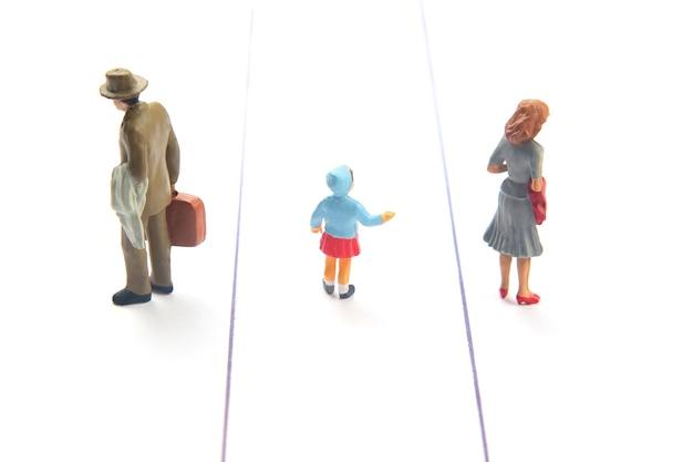 Miniaturowy dzieciak w środku rozdziela rodziców na białym tle.