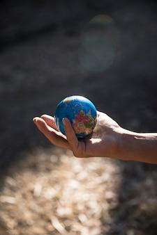 Miniaturowy glob w ręku w przyrodzie