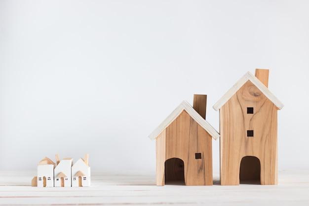 Miniaturowy i duży model domu na białym drewnie, kopia przestrzeń