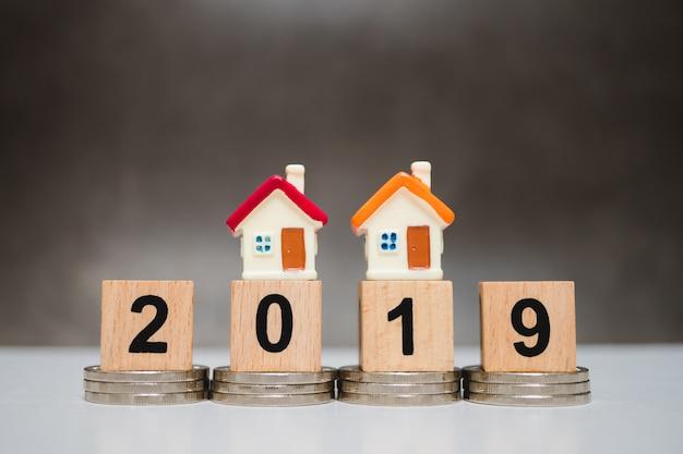 Miniaturowy kolorowy dom na drewnianym bloku roku 2019 i stos monet za pomocą jako conce biznesowych
