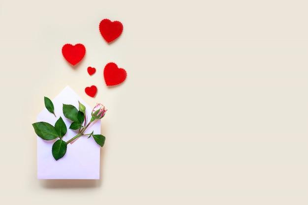 Miniaturowy kwiat róży z liśćmi i sercami leży w kopercie. koncepcja walentynki.