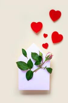 Miniaturowy kwiat róży z liśćmi i sercami leży w kopercie. na jasnym tle. koncepcja walentynki.