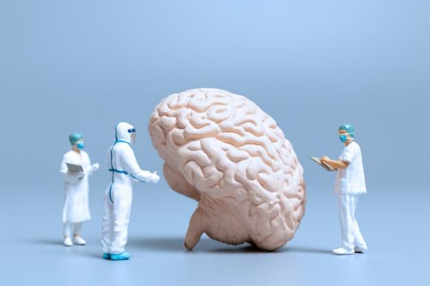 Miniaturowy lekarz sprawdza i analizuje chorobę alzheimera i demencję mózgu, pojęcie nauki i medycyny