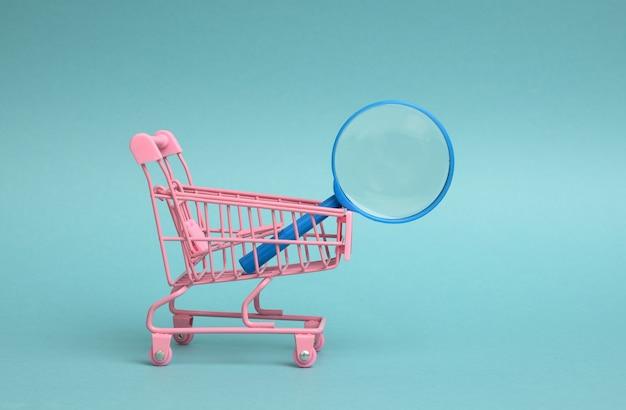Miniaturowy metalowy różowy wózek i czarna plastikowa lupa na jasnoniebieskim tle. pojęcie wyszukiwania i selekcji zakupów, oszczędności