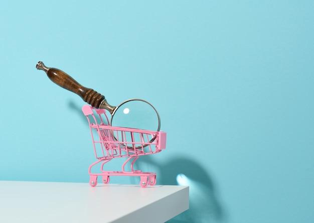 Miniaturowy metalowy różowy wózek i drewniana lupa na jasnoniebieskim tle. pojęcie wyszukiwania i selekcji zakupów, oszczędności
