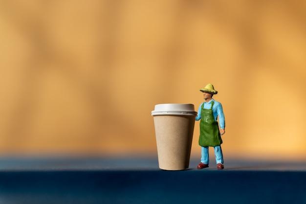 Miniaturowy mężczyzna i filiżanka kawy na wynos