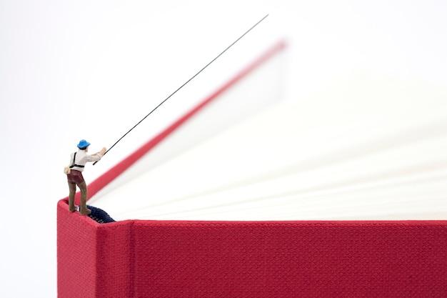 Miniaturowy mężczyzna łowi na książce
