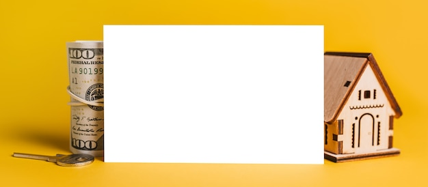 Miniaturowy model domu i pieniądze z pustym tłem na żółtym tle. inwestycje, nieruchomości, dom, mieszkania