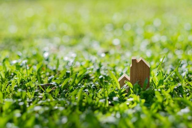 Miniaturowy model domu na tle trawy