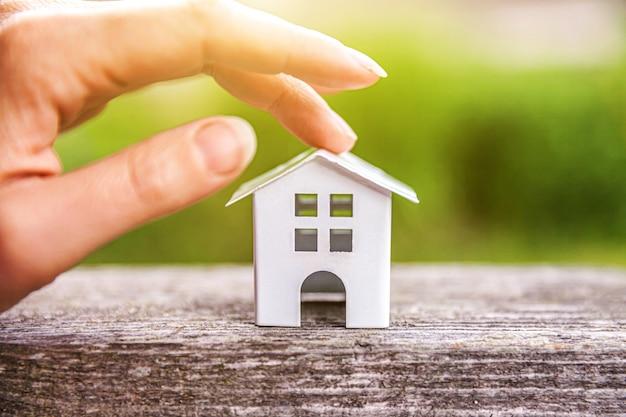Miniaturowy model domu w drewnianym stole w pobliżu zielonego stołu i kobiecej ręki