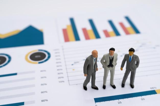 Miniaturowy model ludzi biznesu współinwestujących stojących na wykresie raportu biznesowego