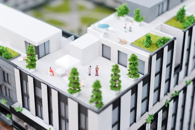 Miniaturowy model, miniaturowe budynki zabawkowe, samochody i ludzie. miasto maquette. nowy projekt budowlany