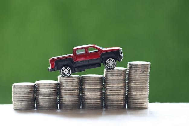 Miniaturowy model samochodu na rosnącym stosie monet na zielonym tle przyrody, oszczędność pieniędzy na samochód, finanse i pożyczka samochodowa, koncepcja inwestycyjna i biznesowa