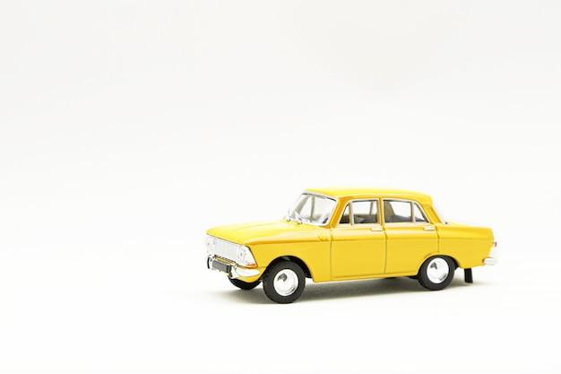 Miniaturowy model żółtego samochodu retro na białej powierzchni
