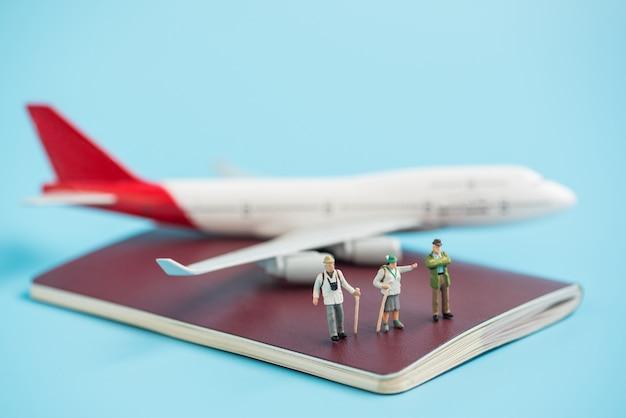 Miniaturowy podróżnik i model samolotu na książce paszportowej