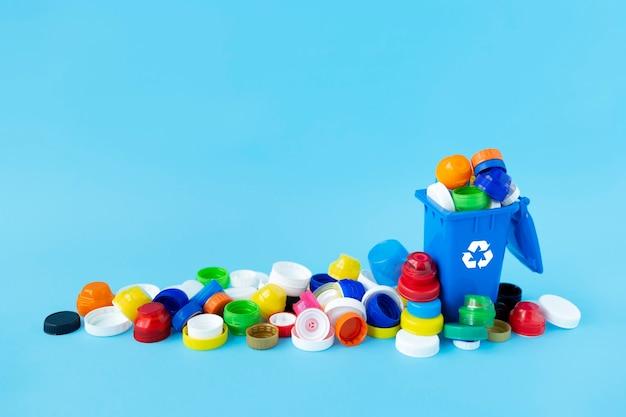 Miniaturowy pojemnik do recyklingu wypełniony plastikowymi nakrętkami do butelek o różnych rozmiarach, kształtach i kolorach na jasnoniebieskim tle.