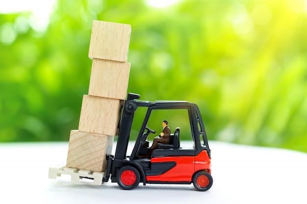 Miniaturowy pracownik transportuje drewnianego blok.