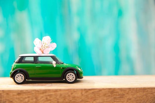 Miniaturowy samochód na tle kwitnie drzewo w wiośnie.