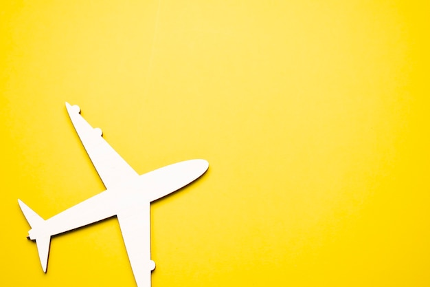Miniaturowy samolocik na żółtym tle. podróż samolotem.