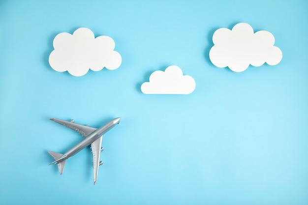 Miniaturowy samolot nad błękitnym tłem z chmurami
