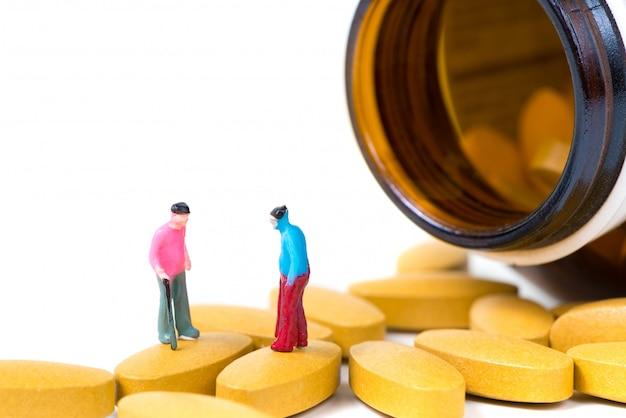 Miniaturowy starzec lub pacjent trzymając laskę z tabletką witaminy c.