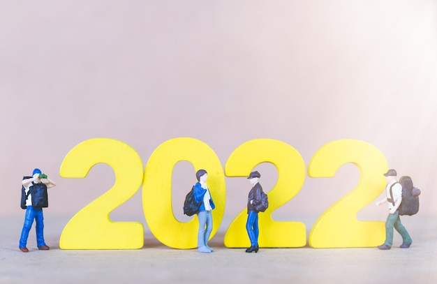 Miniaturowy turysta stojący na drewnianym numerze 2022, koncepcja szczęśliwego nowego roku