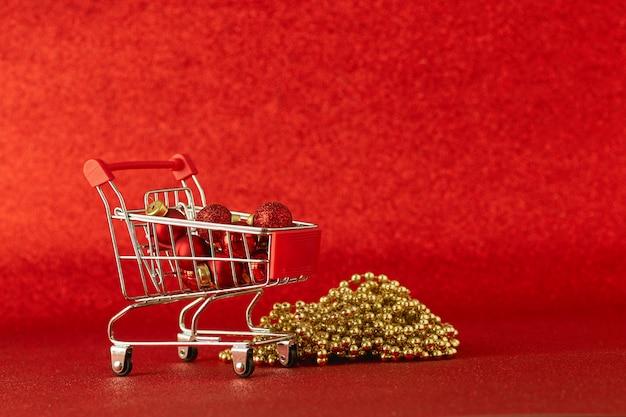 Miniaturowy wózek sklepowy z upominkowymi bombkami i dekoracją