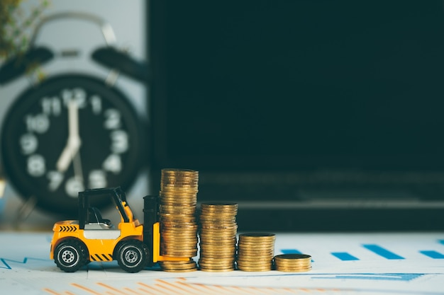 Miniaturowy wózek widłowy ze stosem monet na stole roboczym