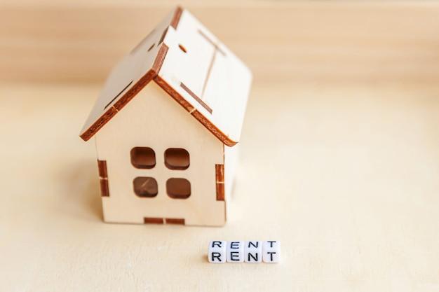 Miniaturowy zabawka modelu dom z napisem wynajem listów słowo na drewnianym tle. eco village, streszczenie ściany środowiska. nieruchomość hipoteki mienia ubezpieczenia słodki domowy ekologia czynszu pojęcie