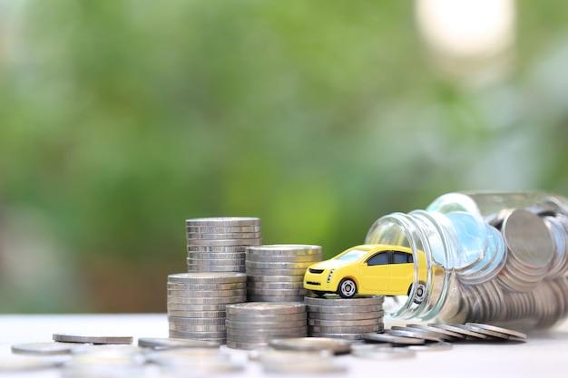 Miniaturowy żółty model samochodu na stosie monet pieniędzy w szklanej butelce