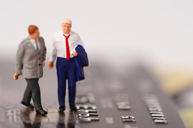 Miniatury człowieka stoją na karcie kredytowej