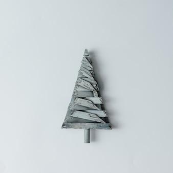 Minimalistyczna choinka wykonana z drewna na białej ścianie. koncepcja nowego roku. leżał na płasko.