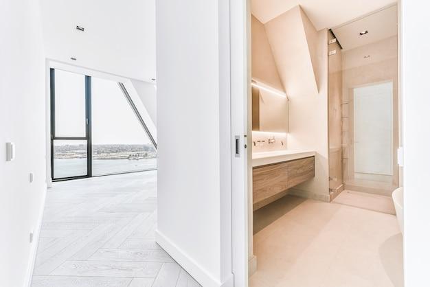 Minimalistyczna drewniana szafka z podwójnymi umywalkami i bateriami ściennymi pod świecącym lustrem