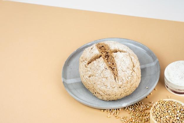 Minimalistyczna izometria projekcji po przekątnej kreatywny beżowe tło z zielonym chlebem gryczanym. szary talerz ceramiczny. nieszkodliwe, zdrowe, bezglutenowe zdrowe wypieki. chleb alternatywny. skopiuj spase.