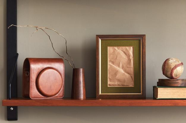Minimalistyczna kompozycja na drewnianej półce z brązową ramką na zdjęcia, zegarem, wazonem, etui na aparat i eleganckimi akcesoriami osobistymi w stylowym wystroju domu.