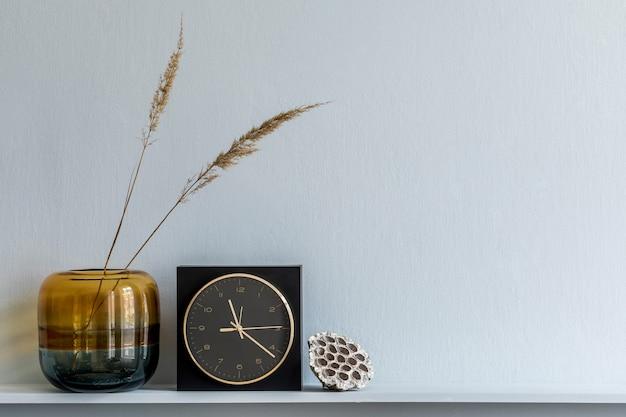 Minimalistyczna kompozycja na drewnianej półce z suszonymi kwiatami w wazonie i eleganckimi dodatkami osobistymi w stylowym wnętrzu salonu. skopiuj miejsce.