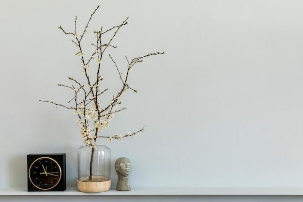 Minimalistyczna kompozycja na półce z suszonymi kwiatami w designerskim wazonie, czarnym zegarem i dekoracją. szara ściana. skopiuj miejsce.