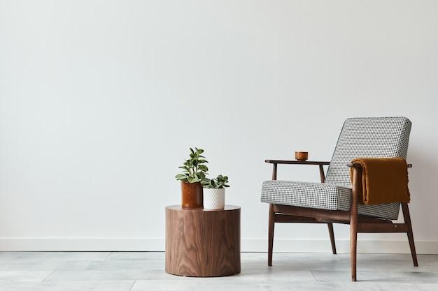 Minimalistyczna kompozycja salonu z designerskim fotelem, drewnianym taboretem, dekoracją, roślinami, przestrzenią do kopiowania i osobistymi dodatkami w nowoczesnym wystroju domu. biała ściana.