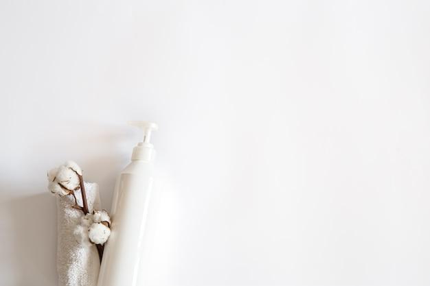 Minimalistyczna kompozycja spa z kosmetykami pielęgnacyjnymi i bawełnianą gałązką miejsca na kopię.