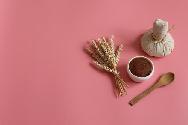 Minimalistyczna kompozycja spa z naturalnym peelingiem, ziołową torbą do masażu, drewnianą łyżką i pszenicą na różowym tle, kopia przestrzeń.