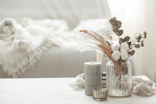 Minimalistyczna kompozycja w stylu skandynawskim z suszonymi kwiatami w wazonie i świecami.