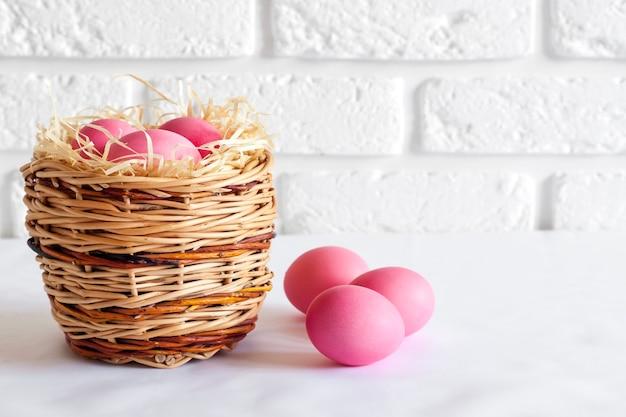 Minimalistyczna kompozycja wielkanocna z wiklinowym koszem i różowymi jajkami na białym tle. skopiuj miejsce