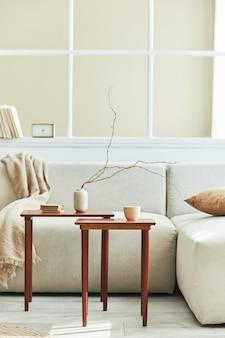 Minimalistyczna kompozycja wnętrza salonu z neutralną sofą, designerskim drewnianym stolikiem, suszonym kwiatem w wazonie, poduszką, oknem, dekoracją i eleganckimi osobistymi akcesoriami w wystroju domu.