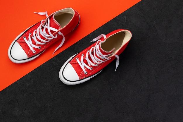 Minimalistyczna kompozycja z letnim obuwiem na czarno-czerwonym tle. płaskie leżały czerwone trampki z widokiem z góry. koncepcja sprzedaży moda zakupy